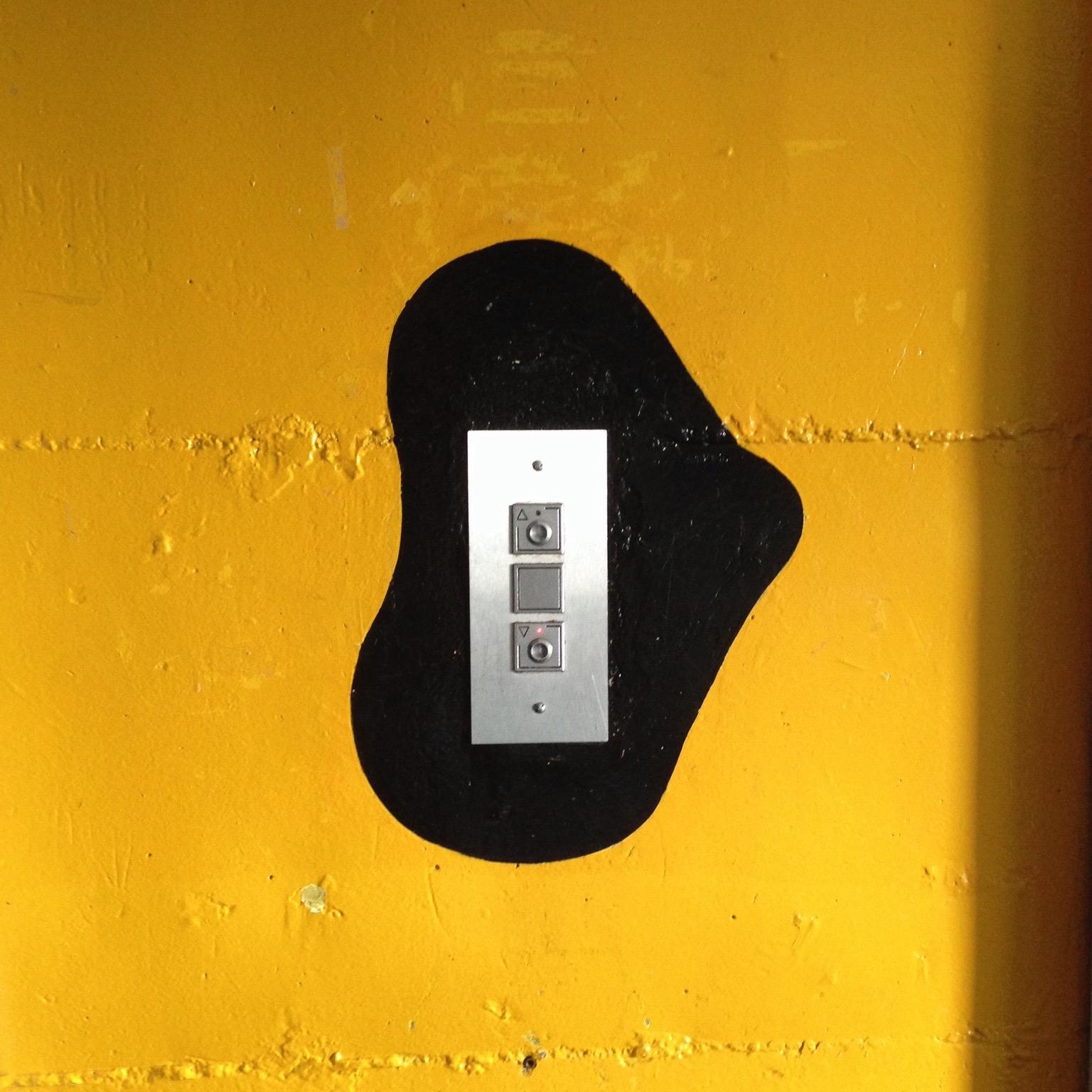 Les boutons d'appel de l'ascenseur sont cerclés d'une tâche noir qui se détache d'un mur jaune vif.