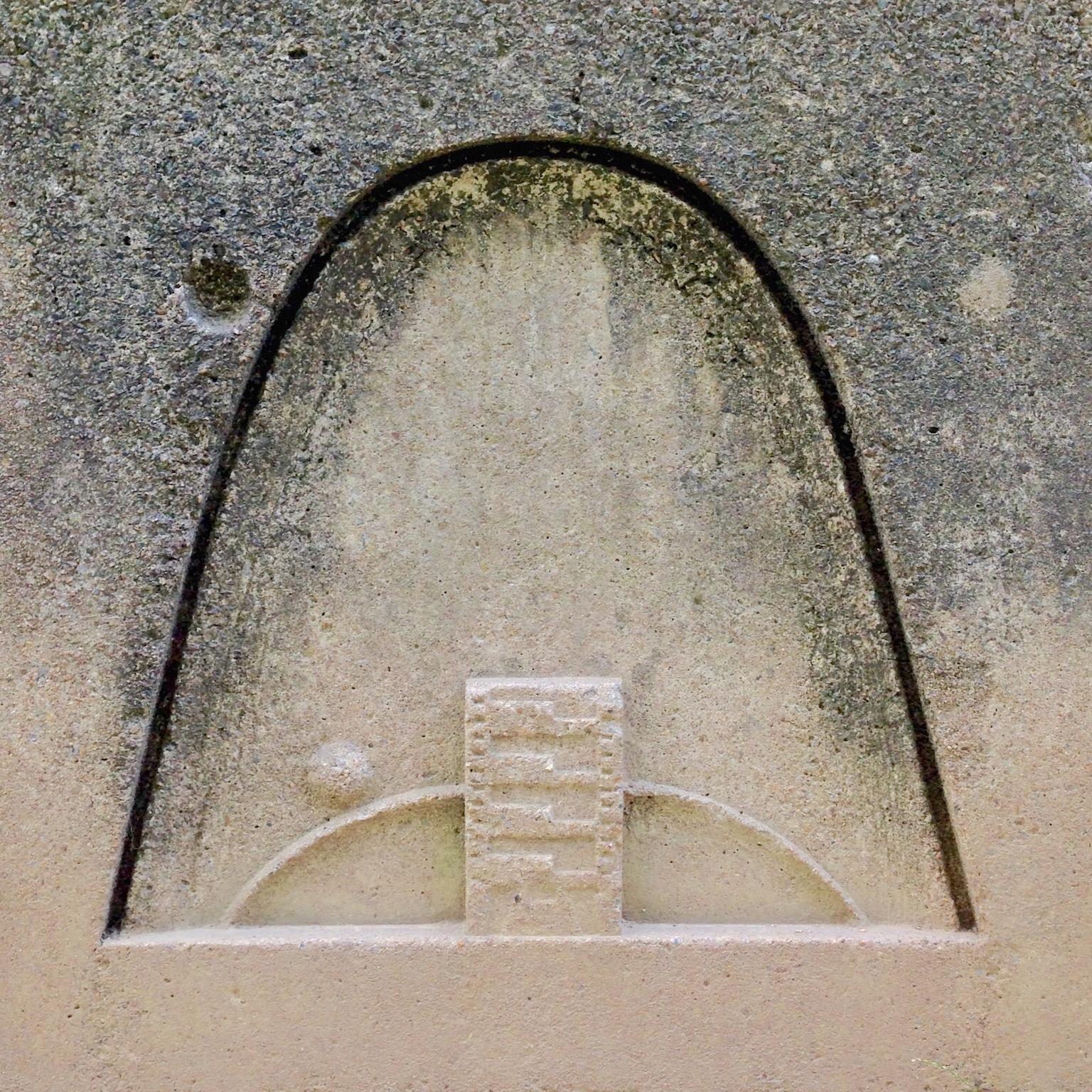 La première pierre posée. L'immeuble est gravé dessus, surmonté par le cycle du soleil.